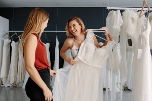 Store assistant helps the bride