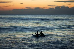 two surfers children talking at sea