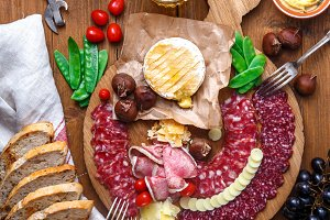Mix of different snacks and appetizers: sausage, bread, olives, cheese, chestnuts, peas and beer on wooden board. Top view.