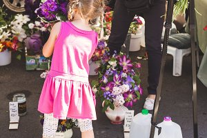 little girl getting market flowers