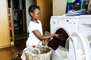 Young girl using washing machine