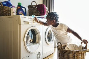 Young girl using washing machine