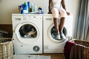 Girl sitting on washing machine