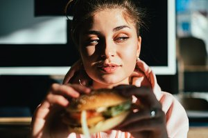 Woman eating tasty hamburger