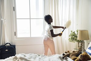 Girl cleaning up the bedroom