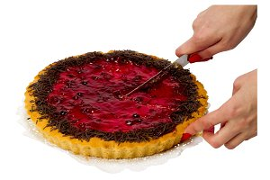 Berry pie cut into slices with a kni