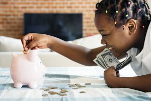 Girl collecting money to piggy bank