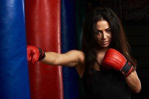 Young girl punching boxing bag