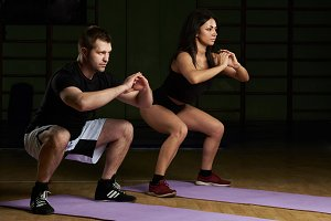 Man and woman doing squat