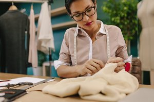 Seamstress hand stitching a designer