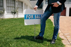 Realtor with a for sale sign board