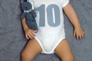 child ten months lying on the bed with a soft toy hare