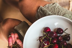 woman eating a bowl of cherries