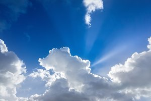 bright sky with sun rays and clouds