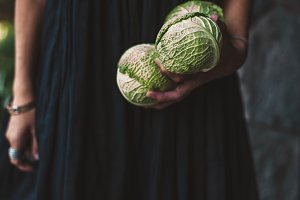 woman holds cabbages