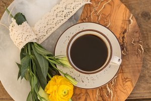 Cup of black coffee and flowers