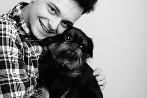 Closeup portrait handsome young hipster man, kissing his good friend black dog isolated light background. Positive human emotions, facial expression, feelings. Black and white photo