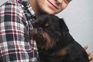 Closeup portrait handsome young hipster man, kissing his good friend black dog isolated light background. Positive human emotions, facial expression, feelings