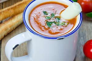 Homemade tomato basil soup in the mug, served with mozzarella cheese stick and croutons, square format