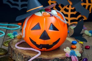 Halloween Jack o Lantern bucket overflowing with candy, spooky Halloween decorations on background, square
