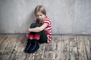 Sad little girl sitting on the floor