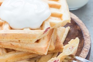 Homemade savory belgian waffles with bacon and shredded cheese, served with plain yogurt on wooden plate, vertical