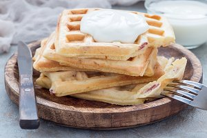 Homemade savory belgian waffles with bacon and shredded cheese, served with plain yogurt on wooden plate, horizontal