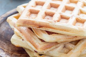 Homemade savory belgian waffles with bacon and shredded cheese, served with plain yogurt, on wooden plate, vertical
