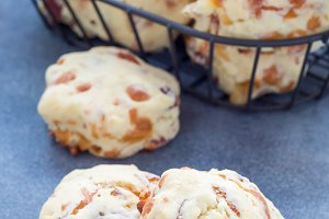 Homemade savory cookies with cheese and bacon in basket and on table, vertical