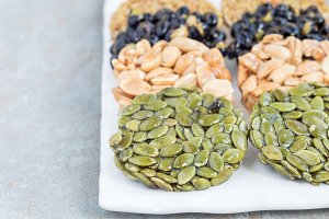 Korean traditional sweet snacks with peanuts, pumpkin seeds, black soybeans and chinese buckwheat on white plate, horizontal, copy space