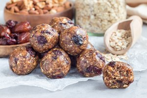 Healthy homemade energy balls with cranberries, nuts, dates and rolled oats on parchment, horizontal