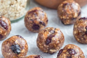 Healthy homemade energy balls with cranberries, nuts, dates and rolled oats on parchment, vertical