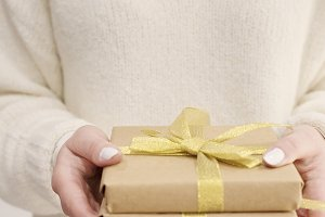Girl with white sweater holding gift