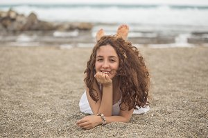Young curly female at the beach