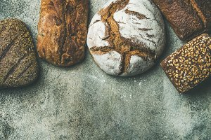 Top view of rustic bread loaves over grey background