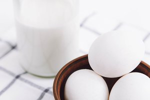 Milk and eggs on white background