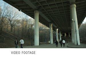 People in blur walking under bridge