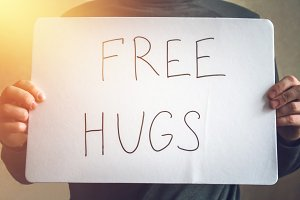 A man holds a note with the inscription - Free hugs. Holiday concept to the International Day of hugs.