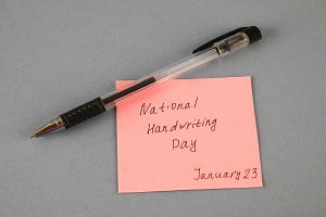 A note with an inscription is a national day of hand writing and a pen on a gray background.