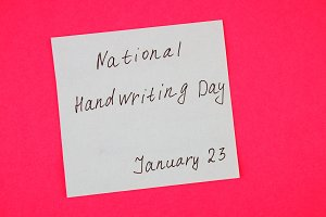 A note with an inscription is a national day of hand writing on a pink background.