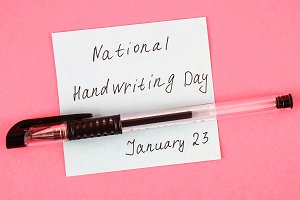 A note with an inscription is a national day of hand writing and a pen.