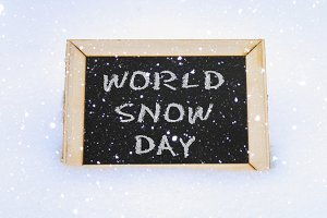 Chalkboard in the snow with the inscription - World Snow Day.