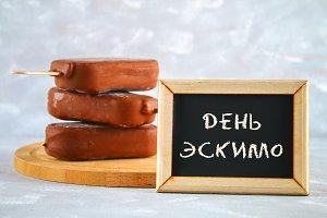 Ice cream eskimo pie on a stick with the text in Russian - Day eskimo pie.