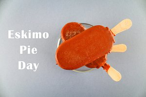Ice cream eskimo pie on a stick with text on a gray background. Concept for the holiday International Eskimo pie day.