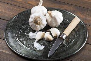 Garlic on metal tray with knife. Food