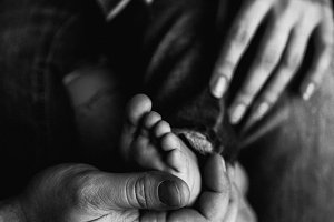 hands of parents and feet of child