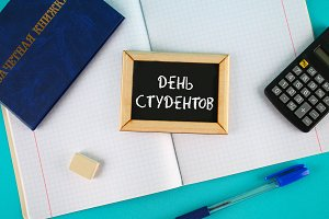 A blue book with an inscription in Russian - a student's record book. Pen, calculator and blank notebooks on a blue background. Inscription in Russian - Students Day.