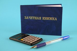 A blue book with an inscription in Russian - a student's record book. Pen, calculator on a blue background. Students Day.
