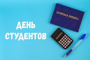 A blue book with an inscription in Russian - a student's record book. Pen, calculator on a blue background. Inscription in Russian - Students Day.