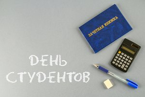 A blue book with an inscription in Russian - a student's record book. Pen, calculator on a gray background. Inscription in Russian - Students Day.